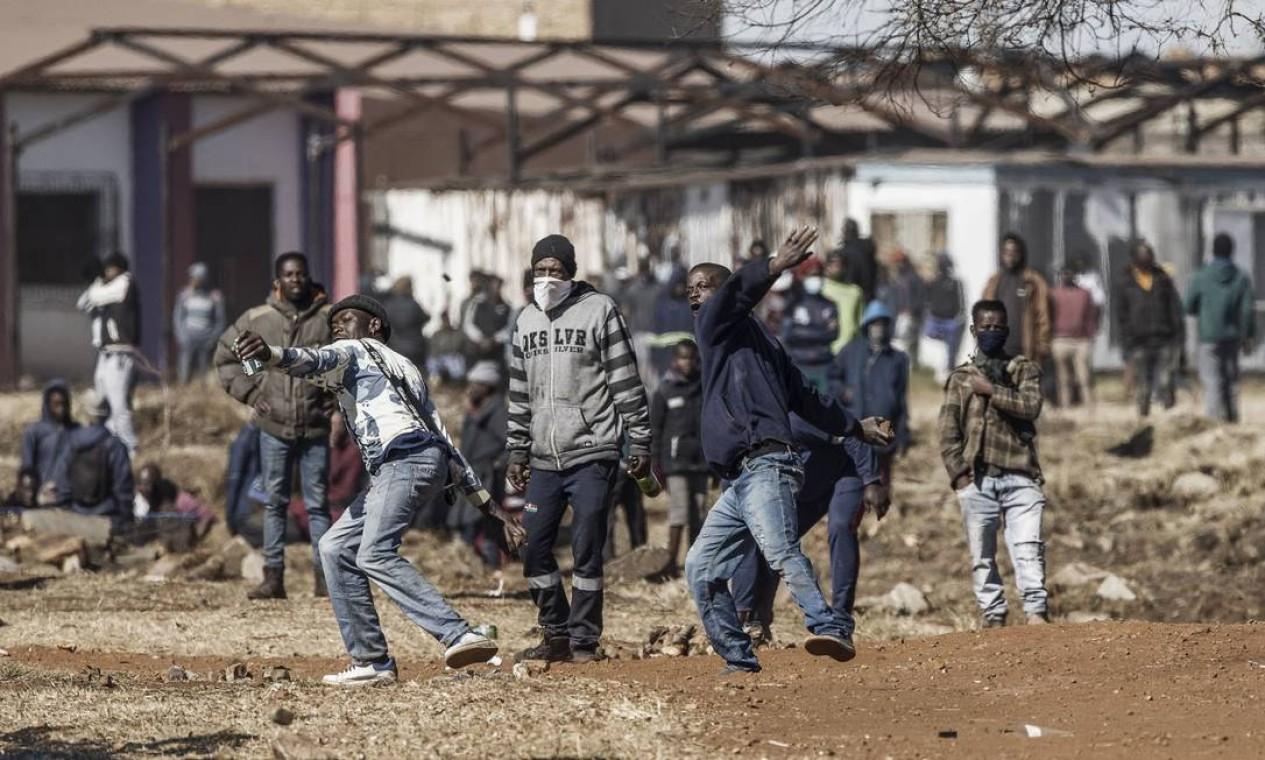 Pessoas confrontam a polícia em frente a um shopping que foi saqueado em Vosloorus, na província de Gauteng Foto: MARCO LONGARI / AFP
