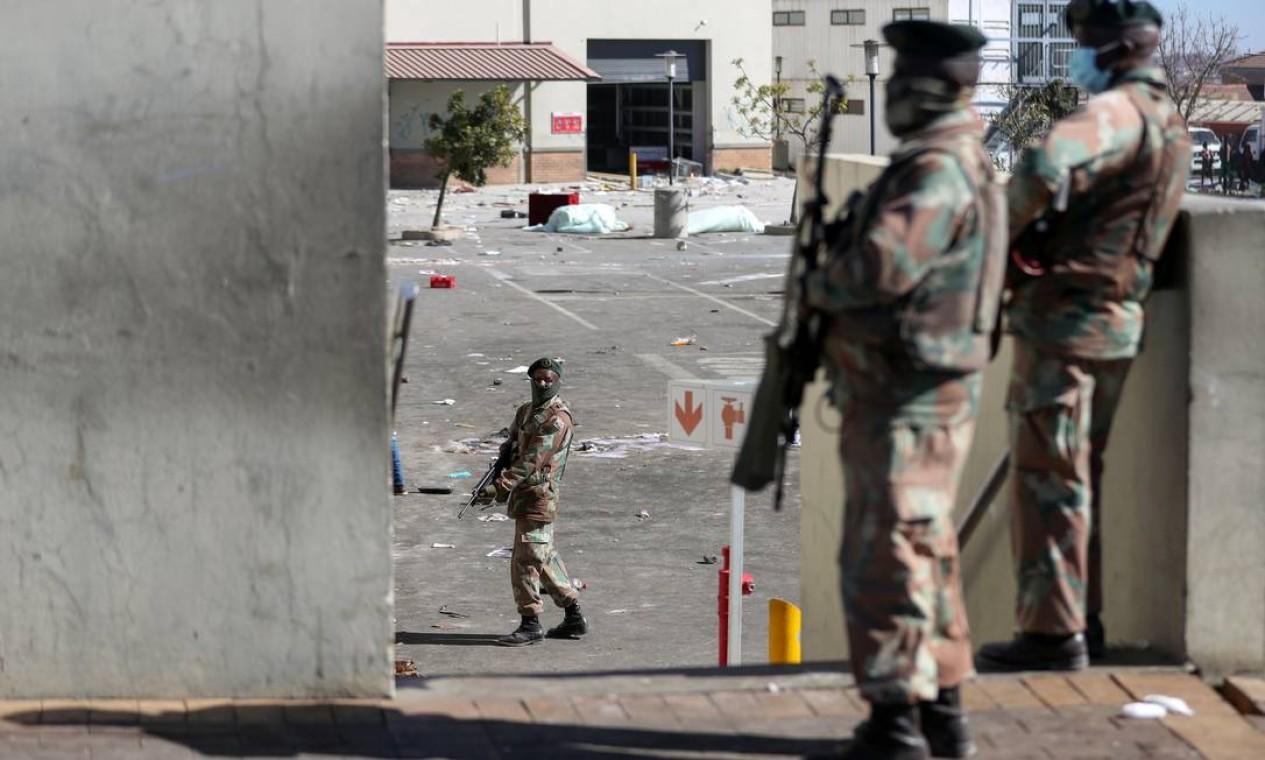 Militares mantêm guarda do lado de fora das lojas saqueadas enquanto em Soweto Foto: SIPHIWE SIBEKO / REUTERS
