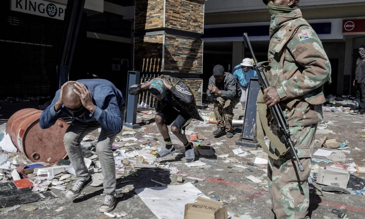 Soldados da Força de Defesa Nacional da África do Sul (SANDF) e oficiais do Serviço de Polícia da África do Sul detêm supostos saqueadores no Jabulani Mall, em Soweto Foto: LUCA SOLA / AFP