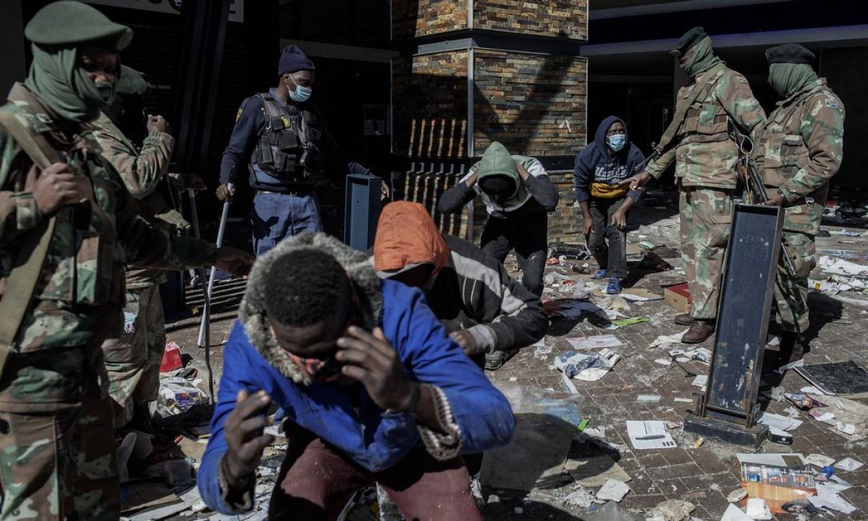 Suspeito de saques no Jabulani Mall, em Soweto, são detidos por agentes de segurança Foto: LUCA SOLA / AFP