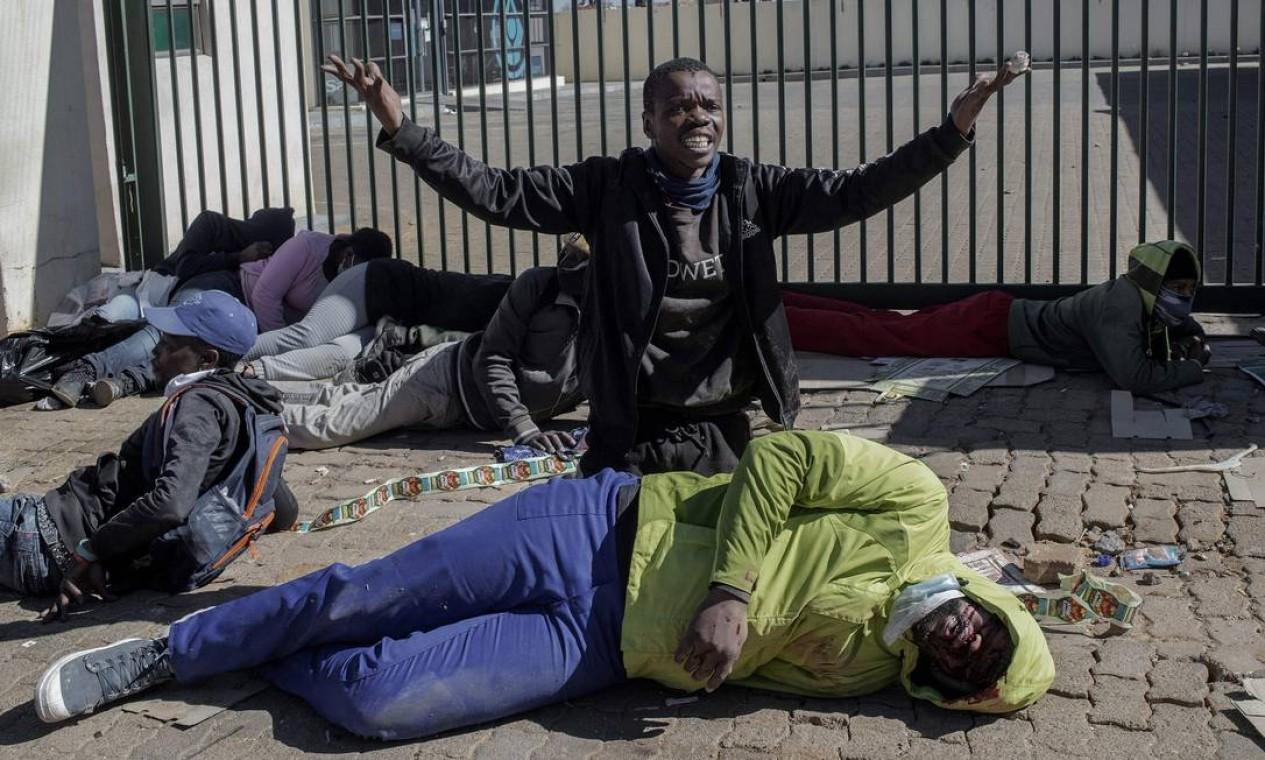 Homem clama por socorro para companheiro ferido por tiro de bala de borracha que teria sido disparada por seguranças do Jabulani Mall em Soweto, nos arredores de Johanesburgo Foto: LUCA SOLA / AFP