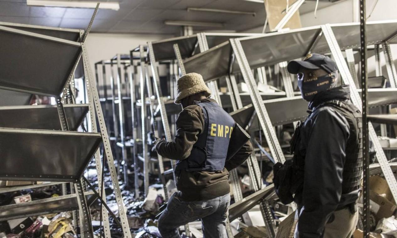 Policiais da África do Sul inspecionam os danos em um shopping saqueado em Vosloorus Foto: MARCO LONGARI / AFP