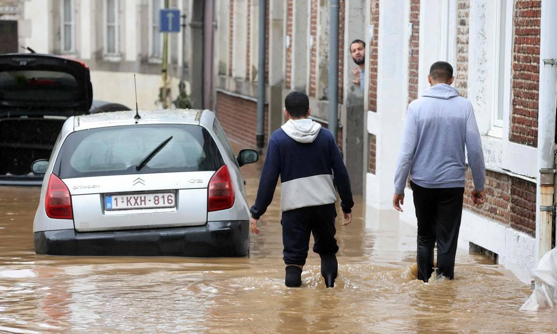 Pessoas caminham na enchente no município belga de Hognoul Foto: FRANCOIS WALSCHAERTS / AFP