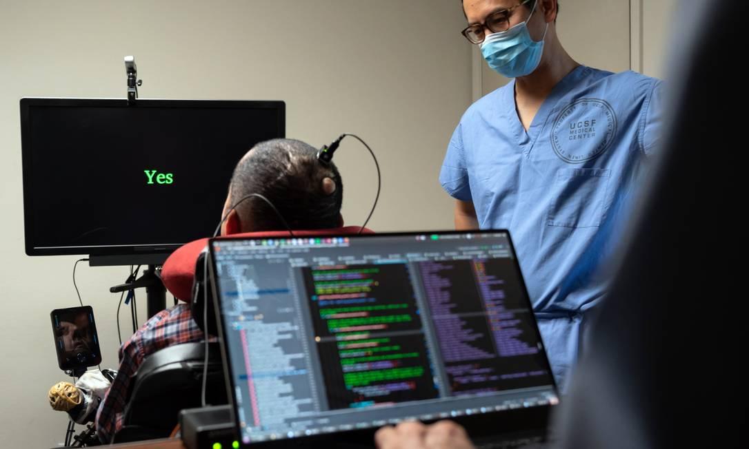 O Dr. Eddie Chang, neurocirurgião da Universidade da Califórnia, Escola de Medicina de São Francisco, ajuda Pancho, um homem paralisado desde os 20 anos de idade, a falar através de um implante no seu cérebro que se liga a um programa de computador Foto: MIKE KAI CHEN / NYT