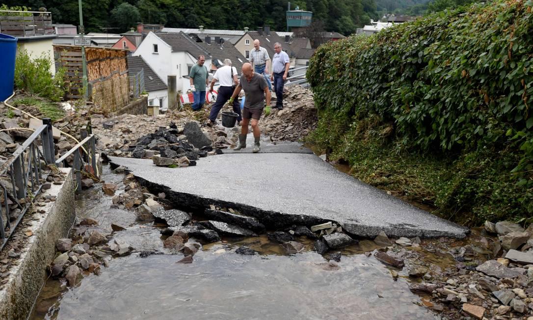 I residenti eliminano le macerie da una strada distrutta durante una tempesta che ha causato ingenti danni ad Hagen, in Germania Foto: INA FASSBENDER / AFP