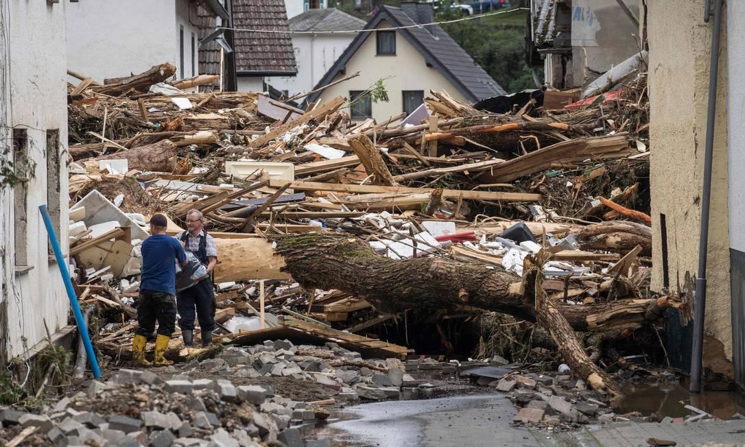 Due uomini cercano di proteggere le proprietà vicine dal relitto di case danneggiate dalle inondazioni a Szold, vicino a Bad Neuenaar, nella Germania occidentale. Foto: BERND LAUTER / AFP