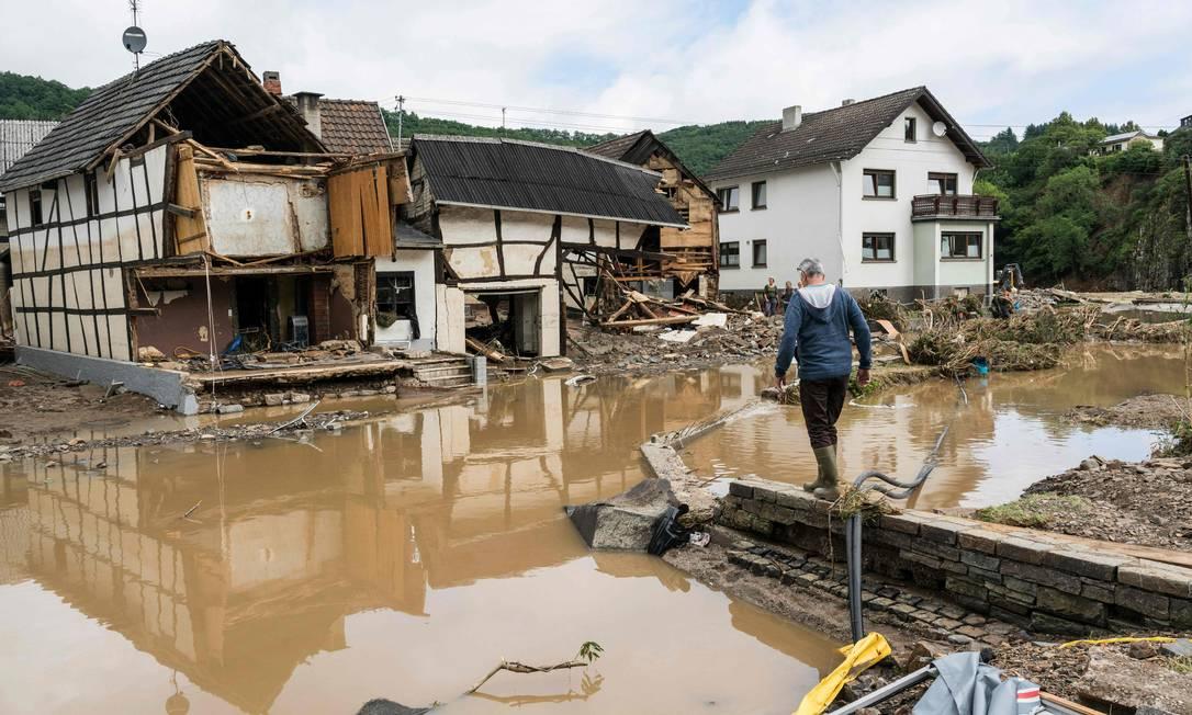 Un uomo cammina per strade allagate e case distrutte dalla pioggia torrenziale a Szold, vicino a Bad Neuenaer, in Germania Foto: BERND LAUTER / AFP