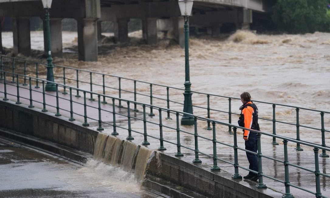 Un poliziotto che osserva l'acqua del fiume Mosa rompe una barricata all'incrocio con Orth, a Liegi. Foto: Anthony Dehes/AFP