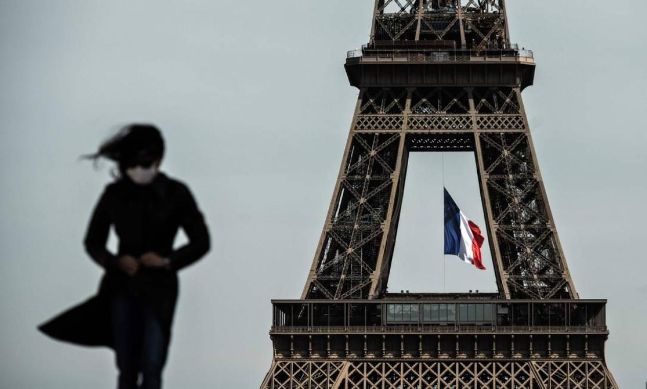 Mulher de máscara caminha perto da Torre Eiffel em 11 de maio de 2020 Foto: PHILIPPE LOPEZ / AFP