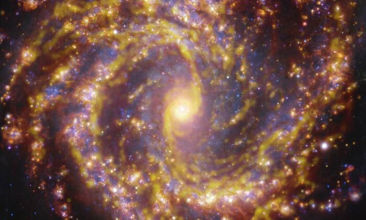 Galáxia NGC 4303 numa combinação de observações do Muse com o Alma. O brilho dourado indica estrelas recém-nascidas, enquanto o azul, assinala as mais velhas Foto: ESO/ALMA (ESO/NAOJ/NRAO)/PHANGS