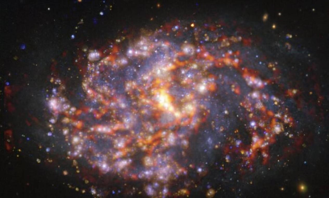 Tons castanho-alaranjados da galáxia NGC 1087, captados pelo Alma, são combinados ao dourado e azul, pelo Muse Foto: ESO/ALMA (ESO/NAOJ/NRAO)/PHANGS