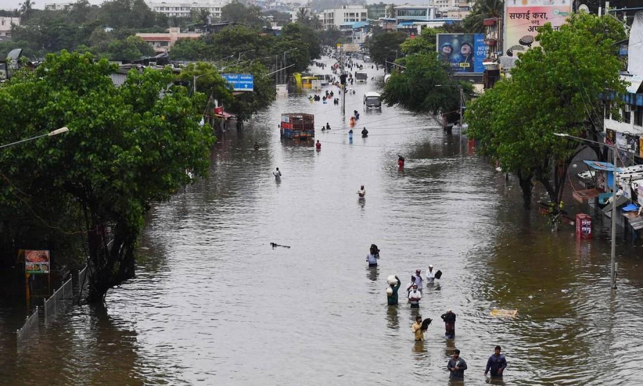 Pessoas caminham ao longo de uma rua inundada após uma forte chuva de monções em Mumbai, na Índia Foto: INDRANIL MUKHERJEE / AFP