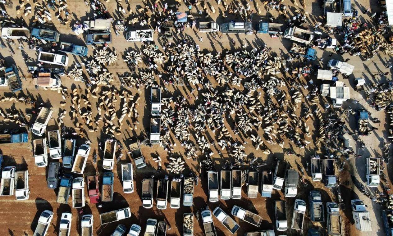 Sírios se reúnem em um mercado de gado para vender e comprar animais de sacrifício nos arredores da cidade de Maaret Misrin, na província de Idlib, no noroeste, antes do Eid al-adha (festa do sacrifício) Foto: ABDULAZIZ KETAZ / AFP