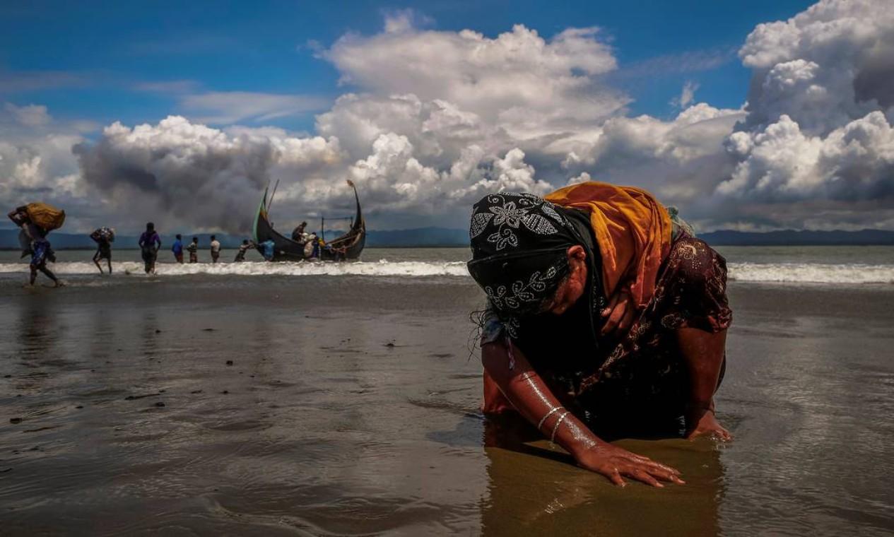 Refugiada Rohingya, considerada a minoria mais perseguida do mundo, é fotografada exausta ao tocar o solo após cruzar a fronteira de Bangladesh-Mianmar de barco pela Baía de Bengala, em Shah Porir Dwip, Bangladesh Foto: DANISH SIDDIQUI / Reuters - 11/09/2017