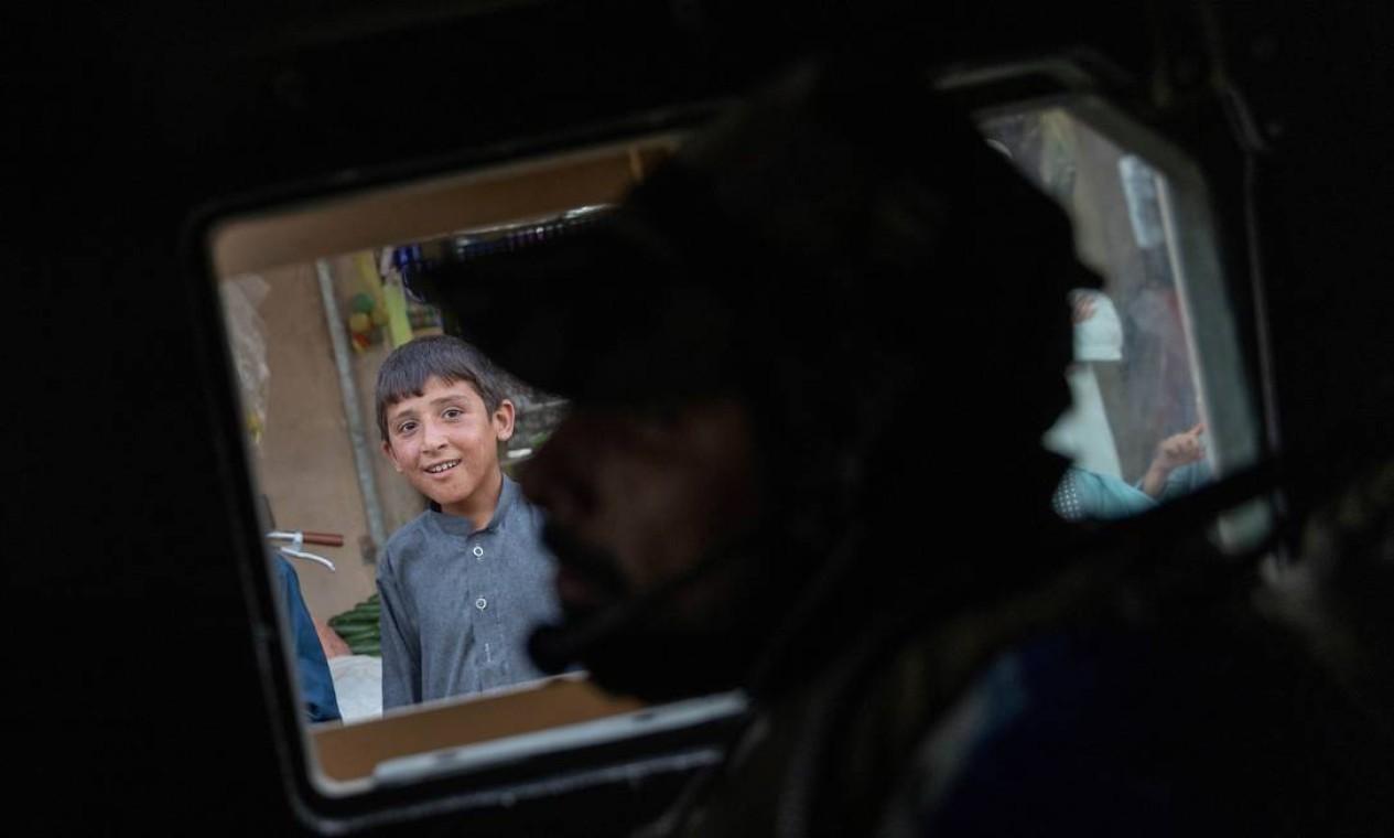 Menino observa o comboio das Forças Especiais Afegãs passar por um mercado durante uma missão de combate contra o Talibã, na província de Kandahar, Afeganistão Foto: DANISH SIDDIQUI / REUTERS - 12/07/2021