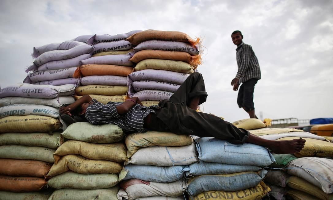 Trabalhador dorme em sacos de areia enquanto outro trabalha em um mercado em Mumbai, Índia Foto: Danish Siddiqui / REUTERS - 21/07/2014