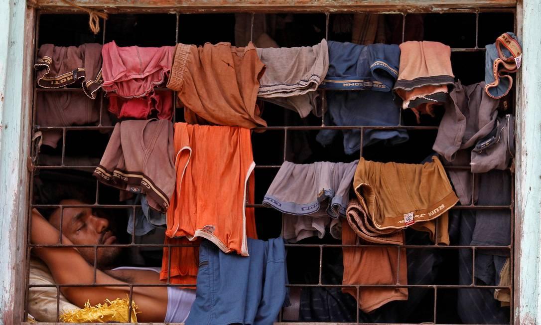 Homem dorme ao lado de uma janela coberta com roupas penduradas para secar, em uma favela em Dharavi, uma das maiores da Ásia, em Mumbai, Índia Foto: Danish Siddiqui / REUTERS - 23/03/2011