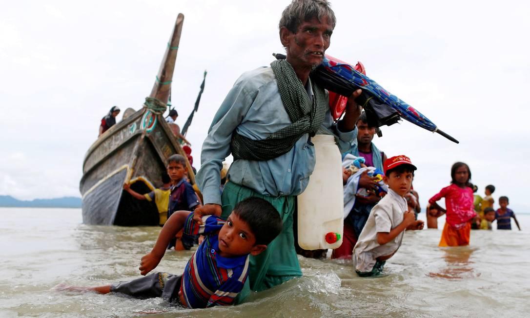 Refugiado Rohingya puxa uma criança enquanto caminham para a costa após cruzar a fronteira entre Bangladesh e Mianmar de barco pela Baía de Bengala Foto: Danish Siddiqui / REUTERS - 10/09/2017