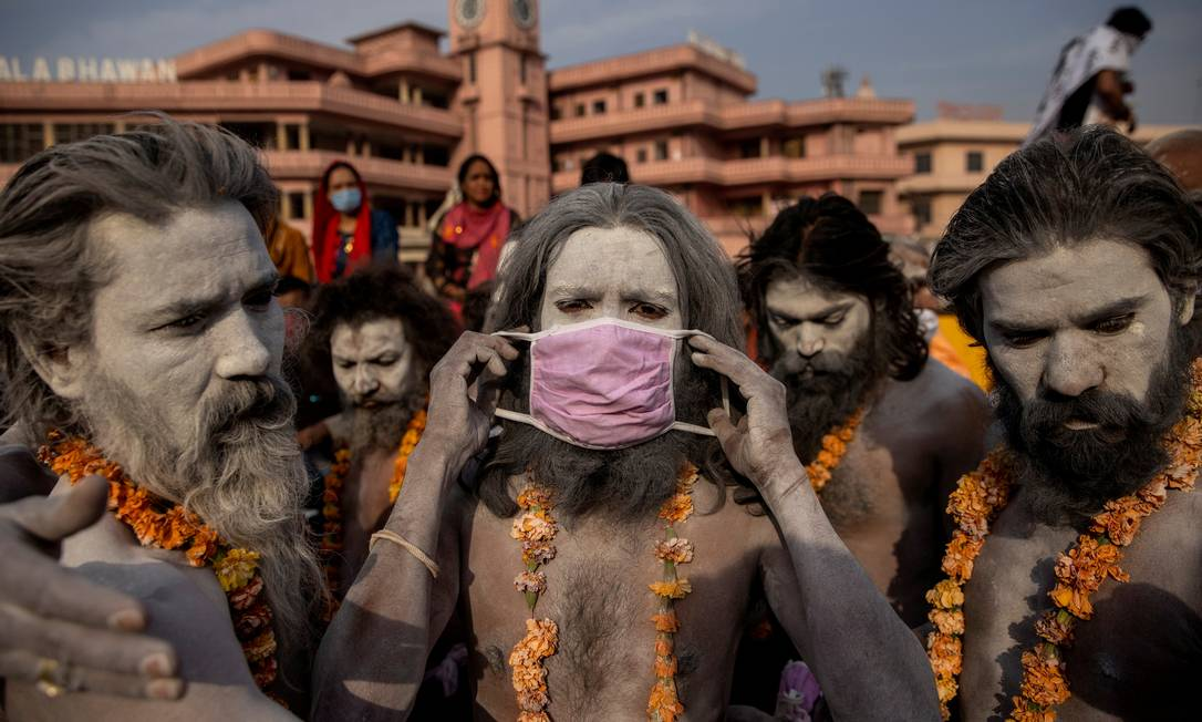 Um Naga Sadhu, ou homem sagrado hindu, veste uma máscara de protreção antes da procissão que termina com um mergulho no rio Ganges, durante o chamado Festival do Jarro, em Haridwar, Índia Foto: Danish Siddiqui / REUTERS - 12/04/2021