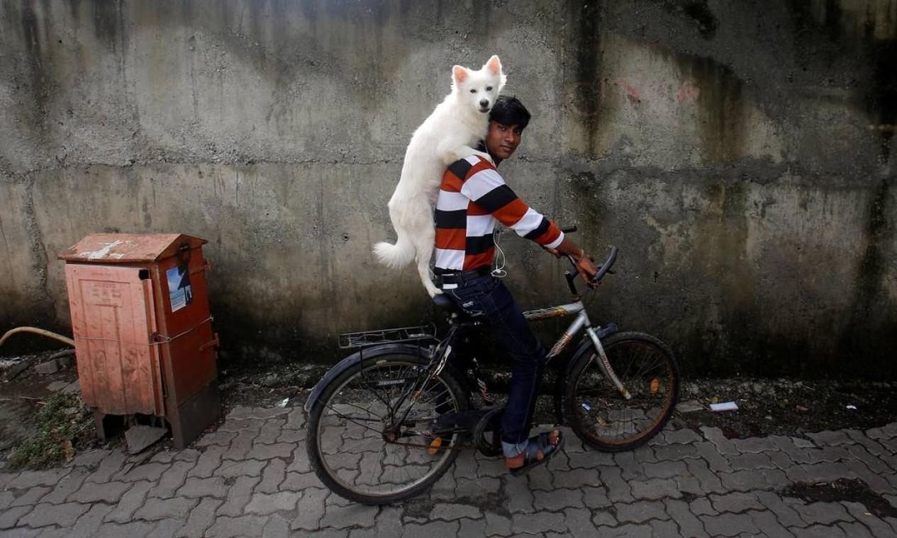 Homem anda de bicicleta carregando seu cachorro nos ombros, em Mumbai, Índia Foto: Danish Siddiqui / REUTERS - 09/07/2013