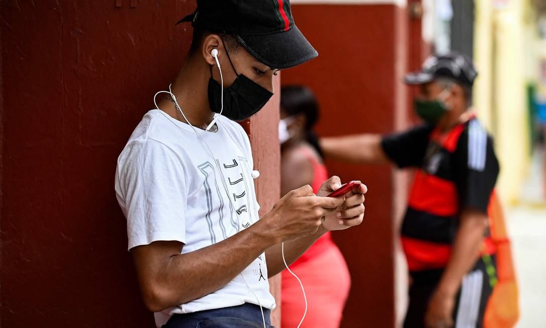 Jovem usa seu celular em Havana após dias sem internet: grupo de opositores é formado por jornalistas, artistas, ativistas e universitários Foto: YAMIL LAGE / AFP