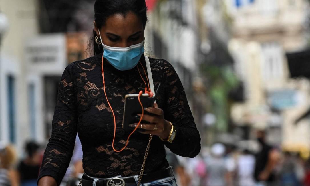 Mulher usa internet no celular nas ruas de Havana: fake news se espalharam na ilha Foto: YAMIL LAGE / AFP
