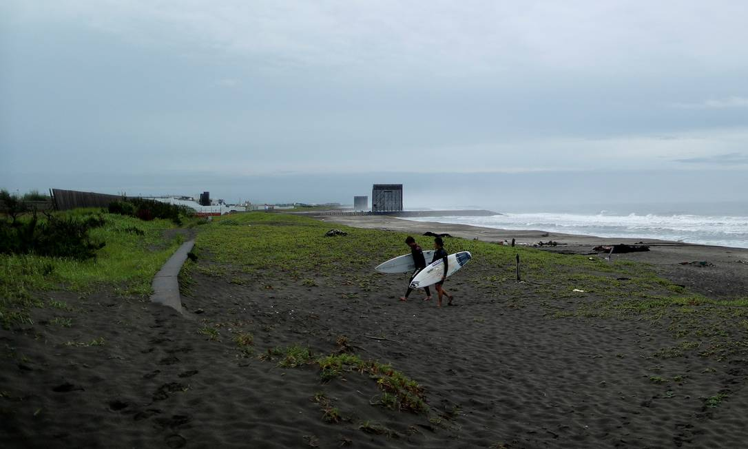 Surfistas caminham na praia de Tsurigasaki, local da competição do surfe, esporte estreante nos Jogos Olímpicos Foto: ISSEI KATO / REUTERS