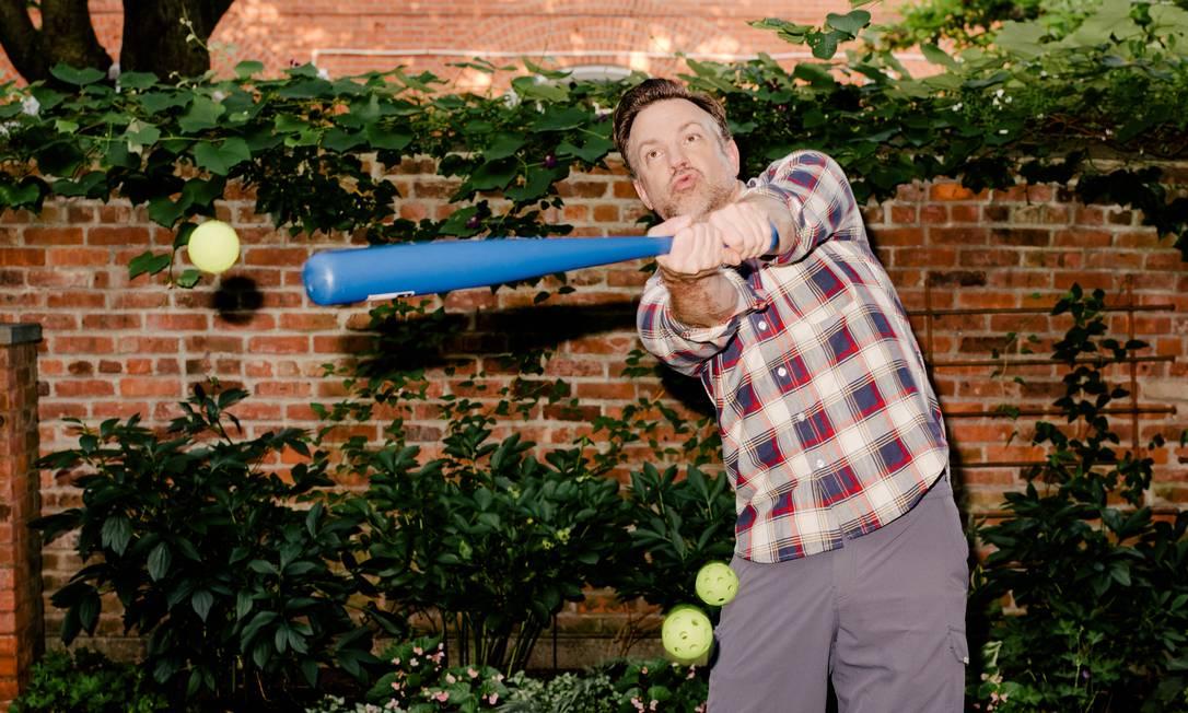 Humor e leveza. Jason Sudeikis, jogando beisebol em sua casa, em Nova York, na série interpreta um técnico de futebol americano que vira treinador de futebol na Inglaterra Foto: DANIEL DORSA / NYT