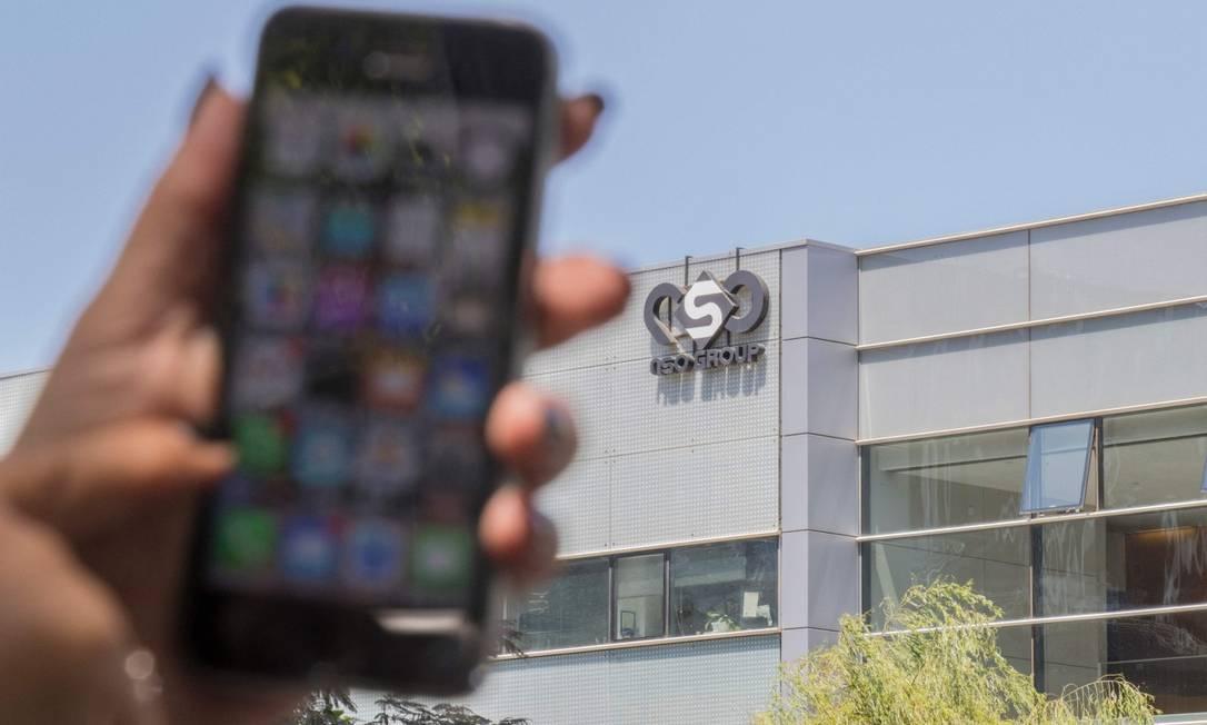 Mulher usa seu iPhone em frente à sede da empresa israelense Pegasus, nos arredores de Tel Aviv Foto: JACK GUEZ / AFP/28-8-16