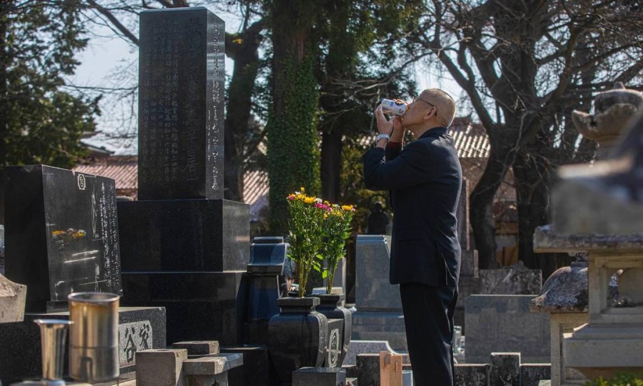 Kimihara reza e toma uma lata de cerveja em uma visita ao túmulo de Tsuburaya , seu falecido companheiro de equipe no Templo Junenji, em Sukagawa Foto: Hiroko Masuike / The New York Times