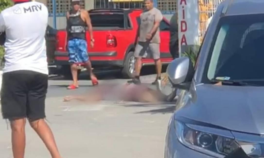 Policial baleado espera socorro no estacionamento de mercado Foto: Reprodução
