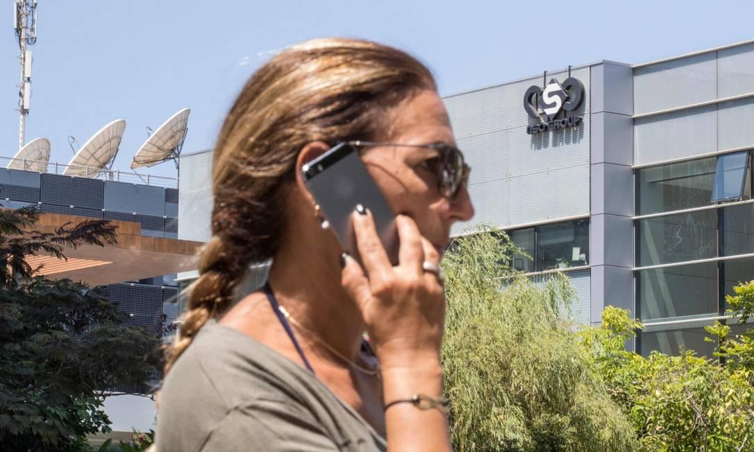 Mulher fala no telefone em frente à sede da empresa israelense NSO, dona do sistema Pegasus Foto: JACK GUEZ / AFP