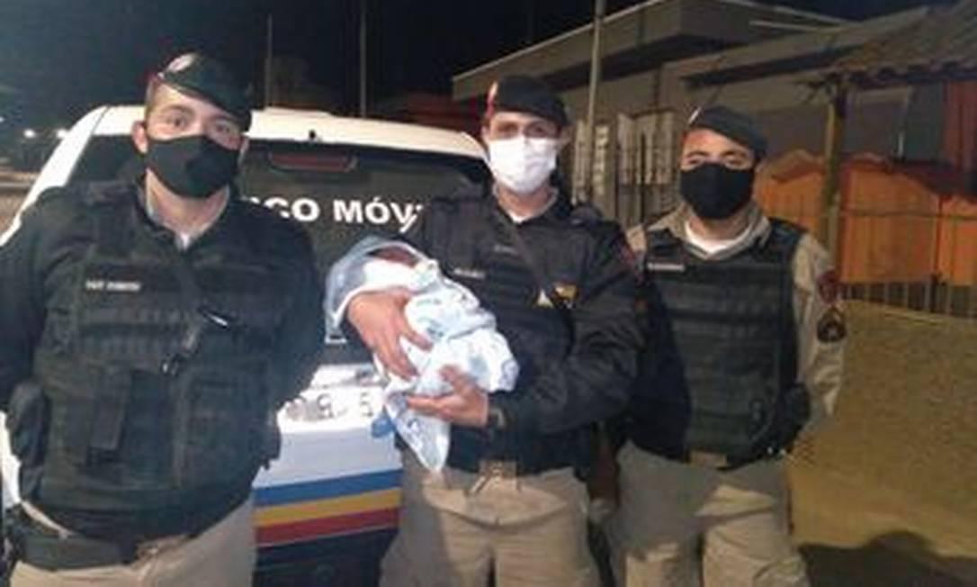 Os PMs posam com o rrecém-nascido que ajudaram a socorrer Foto: Polícia Militar de Minas Gerais / Divulgação