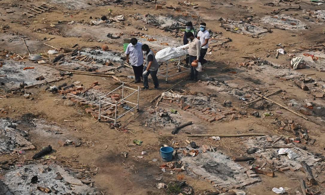 Familiares carregam corpo de vítima da Covid-19 em Nova Déli, na Índia Foto: TAUSEEF MUSTAFA / AFP