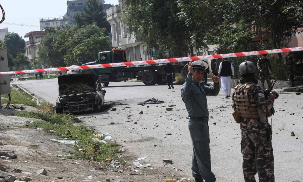 Pessoal de segurança afegão monta guarda perto de um veículo carbonizado do qual foguetes foram disparados que pousou perto do palácio presidencial afegão em Cabul Foto: - / AFP