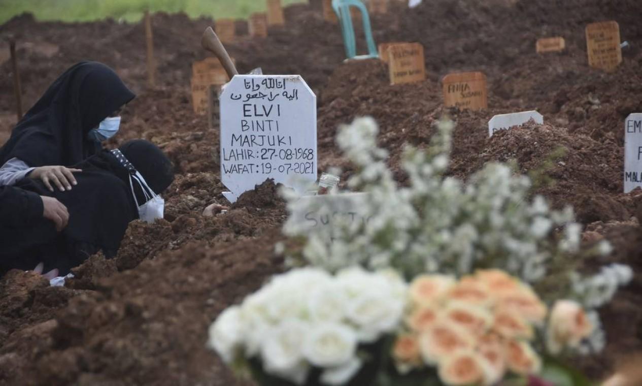Familiar chora ao túmulo de uma vítima de Covid-19, em um cemitério em Bekasi, na Indonésia Foto: REZAS / AFP