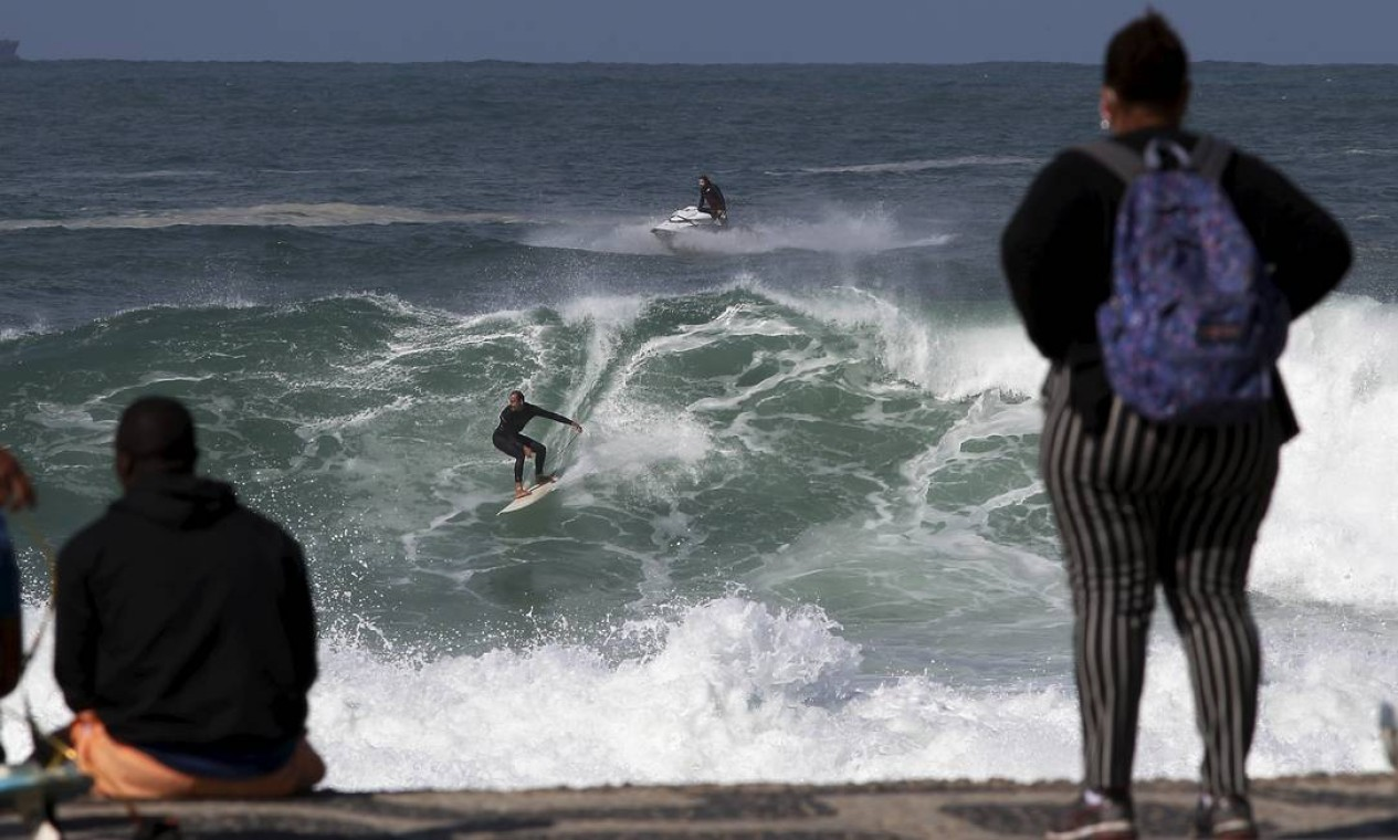 Pessoas observam surfista descendo em onda de 2 metros no Leblon Foto: Fabiano Rocha / Agência O Globo