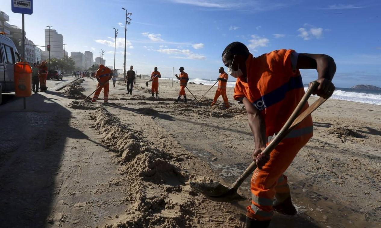 Equipes da Comlurb trabalham para retirar areia do calçadão Foto: Fabiano Rocha / Agência O Globo