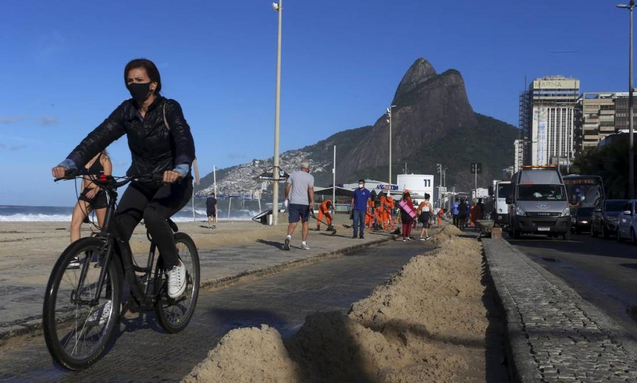 Ciclistas dividiam a pista da ciclovia com a areia acumulada durante a manhã Foto: Fabiano Rocha / Agência O Globo