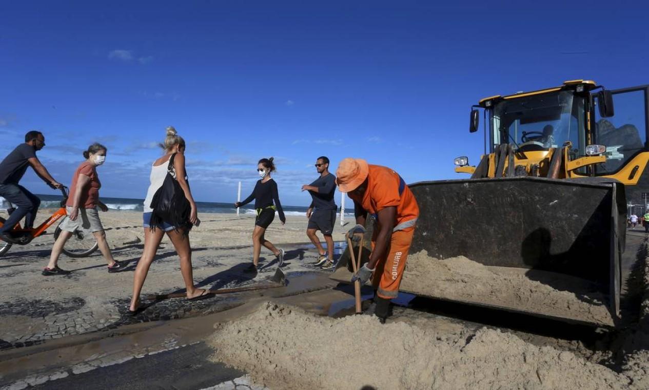 Retroescavadeira é usada para ajudar no serviço de remoção da areia da praia do calçadão e da ciclovia Foto: Fabiano Rocha / Agência O Globo