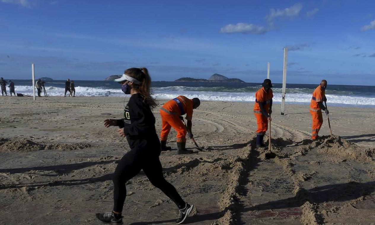 As aparências enganam. Mulher corre em trecho do calçadão totalmente tomado pela areia Foto: Fabiano Rocha / Agência O Globo