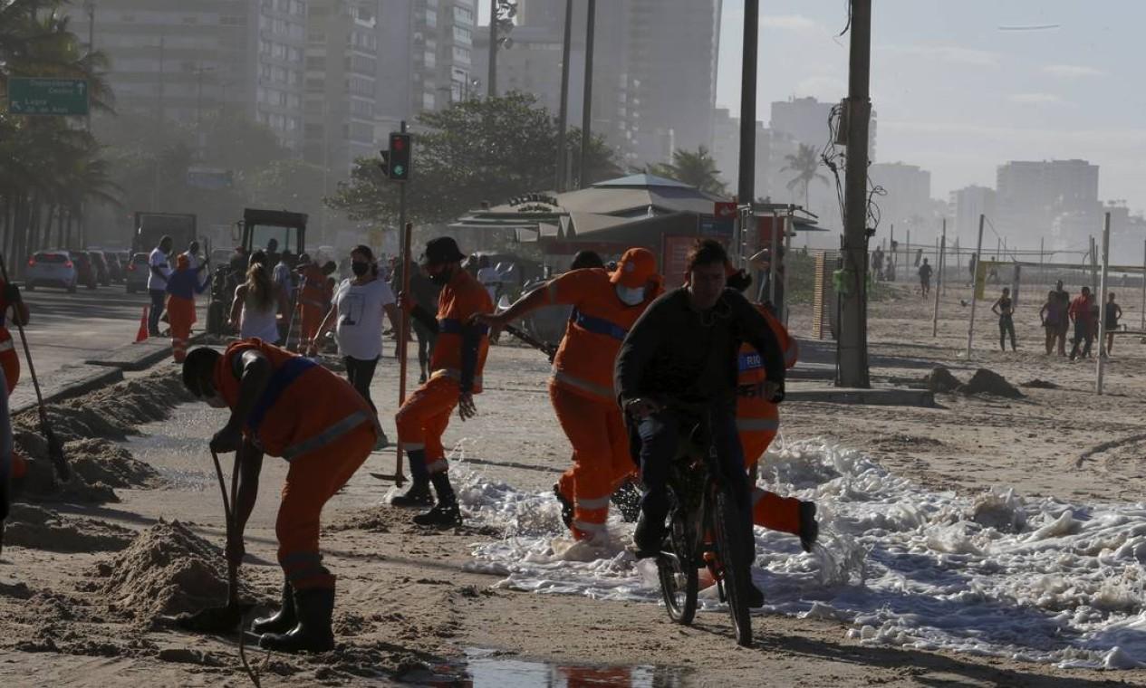 Pessoal da Comlurb é surpreendido pela água do mar que toma conta do calçadão Foto: Fabiano Rocha / Agência O Globo