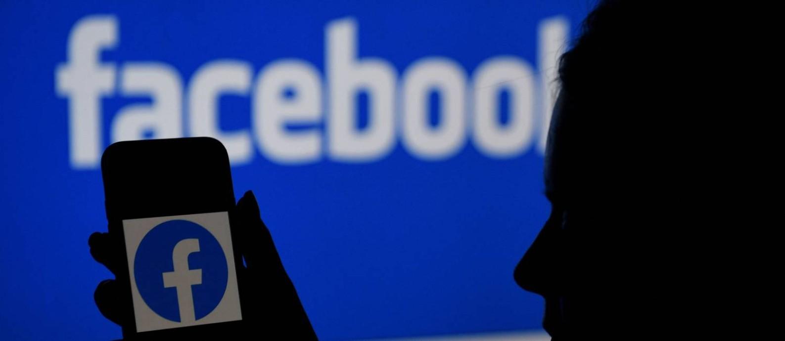 Logo do Facebook é vista na tela de um smartphone Foto: OLIVIER DOULIERY / AFP