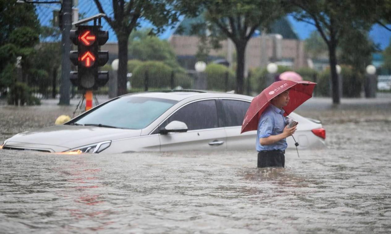 Homem passa por um carro submerso ao longo de uma rua inundada após fortes chuvas em Zhengzhou, na província central de Henan, na China Foto: STR / AFP