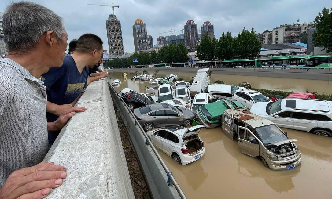 Chineses observam a destruição provocada por indundações em Zhengzhou Foto: STR / AFP