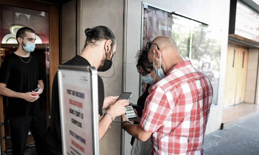 Espectadores têm seu passaporte de saúde verificado antes de entrar no cinema Grand Rex, em Paris Foto: ALAIN JOCARD / AFP