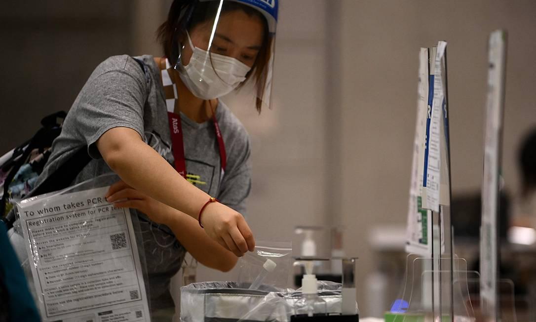 Jornalista deposita amostra de saliva para a realização de teste PCR para Covid-19 em Tóquio: apesar de protocolo, casos positivos vêm aparecendo em atletas Foto: FRANCK FIFE / AFP