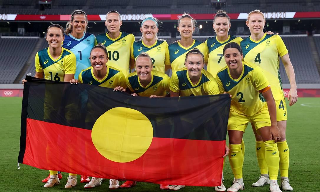 Jogadoras da Austrália posam com bandeira aborígene antes da estreia na Olimpíada de Tóquio Foto: EDGAR SU / REUTERS