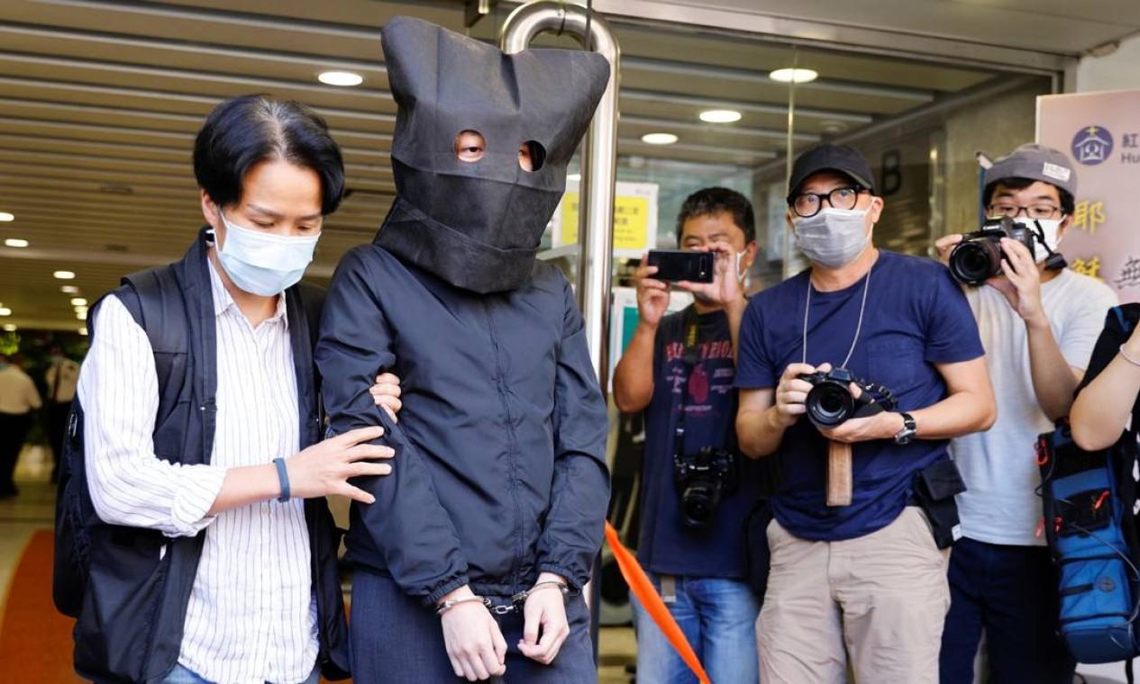 Policial acompanha um dos cinco suspeitos publicação e distribuição de material subversivo, em Hong Kong, China Foto: TYRONE SIU / REUTERS