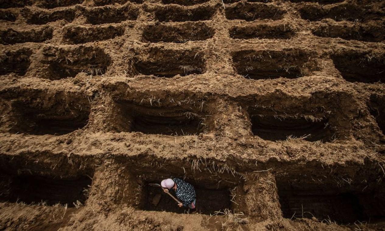 Trabalhador do cemitério cava buracos para as vítimas do coronavírus Covid-19 no cemitério Setu Gede em Bogor, Java Ocidental, Indonésia Foto: ADITYA AJI / AFP